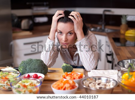 Depressed and sad young woman in kitchen - stock photo