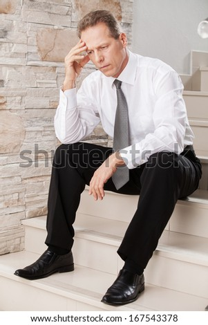 Depressed businessman. Depressed mature man in formalwear holding head in hand while sitting on staircase  - stock photo