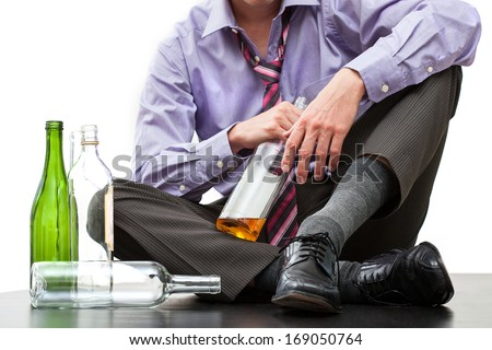 Depressed businessman drinking alcohol on the floor - stock photo