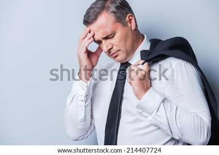 Depressed businessman. Frustrated mature man in formalwear touching head with hand and keeping eyes closed while standing against grey background - stock photo