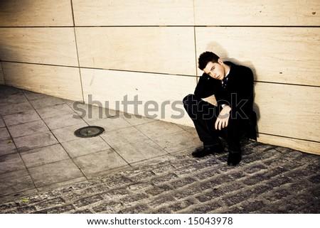 Depressed businessman in urban background - stock photo