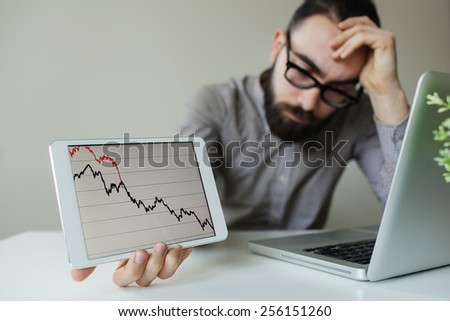 Depressed businessman leaning head below bad stock market chart in office - stock photo