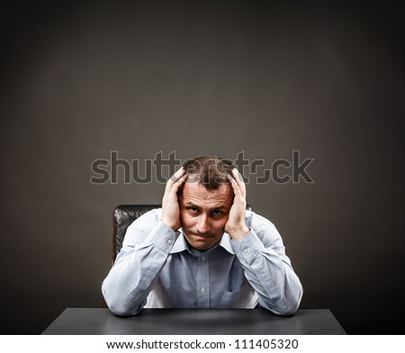 Depressed businessman or white collar worker at his desk holding his head