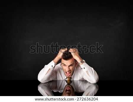 Depressed businessman sitting at a desk - stock photo