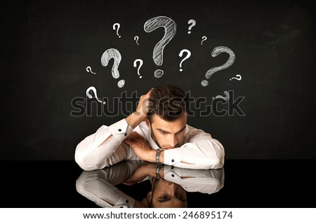 Depressed businessman sitting under question marks - stock photo