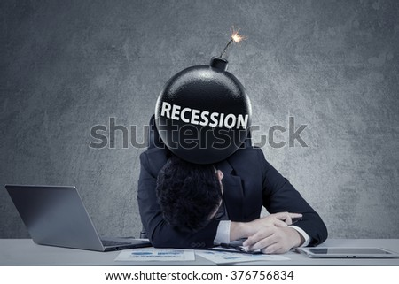 Depressed businessman sleeping on desk with a bomb of economic recession on his head - stock photo