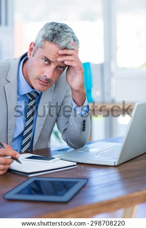 Depressed businessman trying to work in office - stock photo