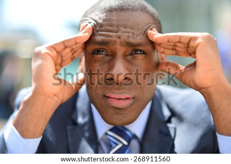 Depressed businessman with hands on his forehead - stock photo