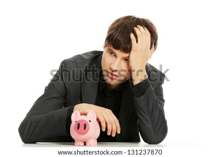 Depressed businessman with piggybank. Isolated on white - stock photo