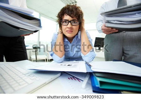 Depressed businesswoman has a lot of work with documents