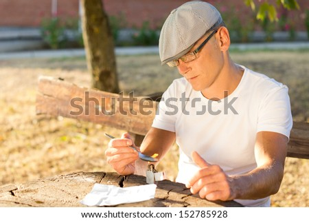 Depressed Caucasian middle-aged man preparing a drug dose in order to get high outdoors - stock photo
