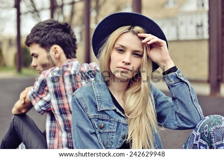 Depressed couple. Depressed young hipsters couple sitting back to each other  - stock photo