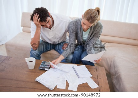 Depressed couple doing their accounting in their living room - stock photo
