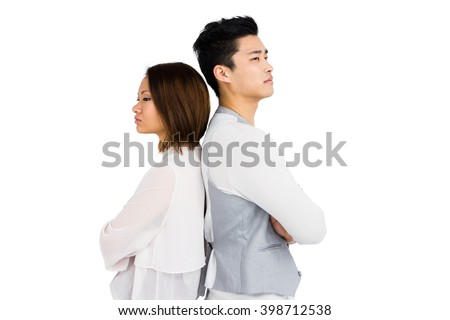 Depressed couple standing back to back on white background - stock photo
