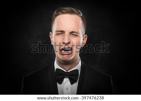 Depressed crying man in black suit over grey background. - stock photo