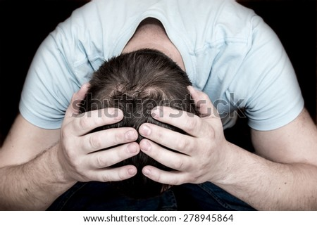 Depressed crying scared man holding his head in his hands sitting on floor over black background. Despair, depression, hopelessness, addiction concept. - stock photo