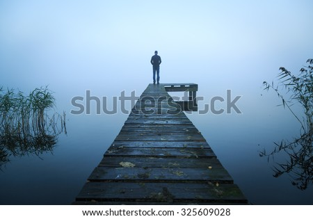 Depressed emotions concept: man standing at the end of a jetty, on a foggy, autumn morning. - stock photo