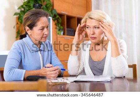 Depressed female pensioners discussing finances indoor. Focus on the left woman