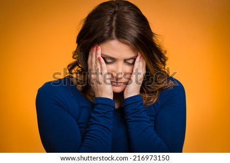 Depressed, gloomy. Closeup portrait unhappy middle age woman head on hand bothered by mistake situation having bad headache isolated orange background. Negative human emotion facial expression feeling - stock photo