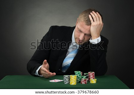 Depressed Male Poker With Chips And Cards On Table
