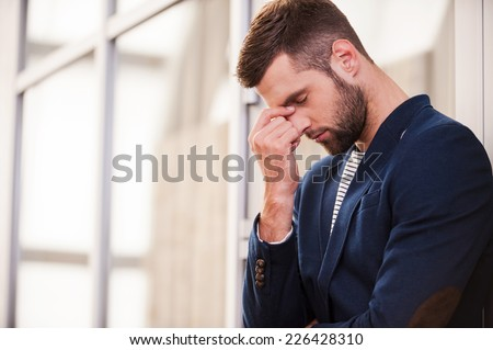 Depressed man. Frustrated young man in smart casual wear touching his face with hand and keeping eyes closed while standing indoors  - stock photo