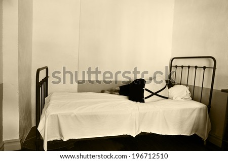 Depressed man in bed in a mental hospital. - stock photo