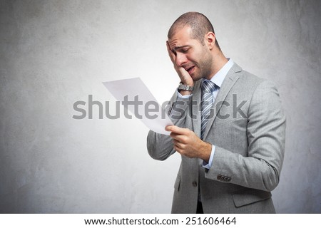 Depressed man reading a document - stock photo