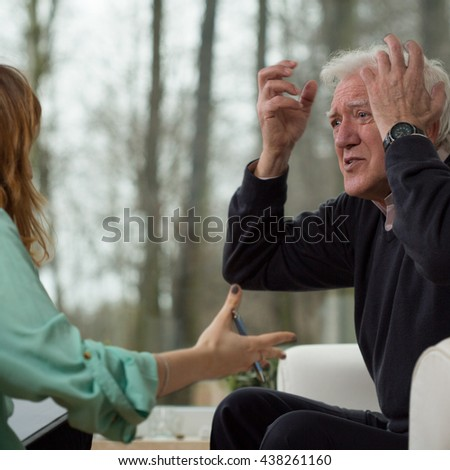 Depressed man showing his emotions during psychotherapy session - stock photo