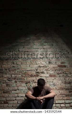 Depressed man sitting alone against brick wall. - stock photo