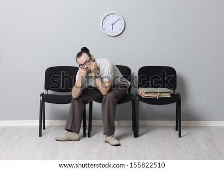 Depressed Man sitting alone in a waiting room for an appointment - stock photo