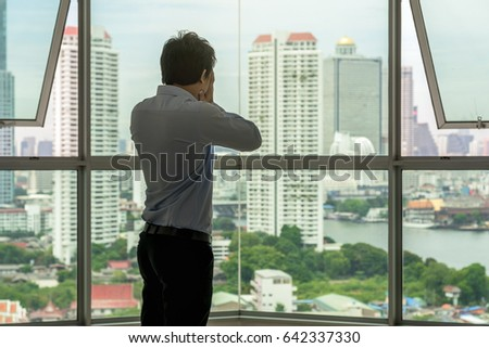 depressed man standing face in hands on the interior Skyscraper with low light environment beside the windows over the cityscape background, dramatic concept