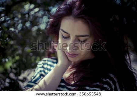 depressed melancholic girl in a forest in autumn, red long hair - stock photo