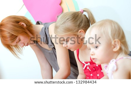 Depressed mother with her two daughters - stock photo