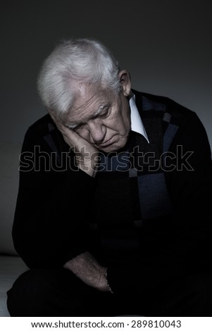 Depressed old man sitting alone in darkness