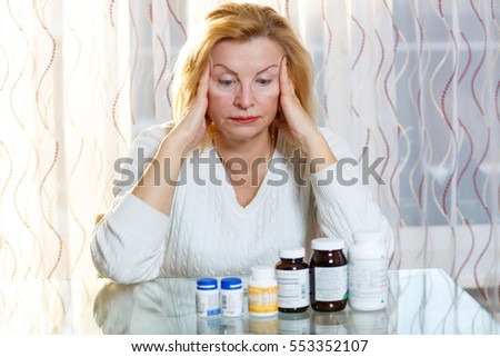 Depressed old senior woman with medicine or health problem. Looking on bottle with pills