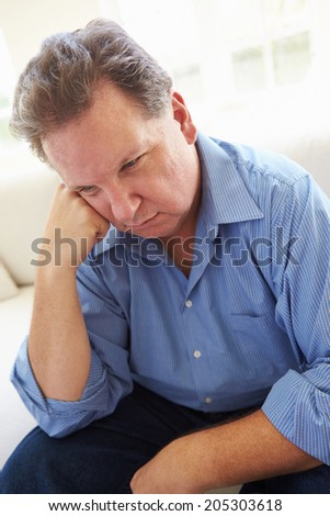 Depressed Overweight Man Sitting On Sofa - stock photo