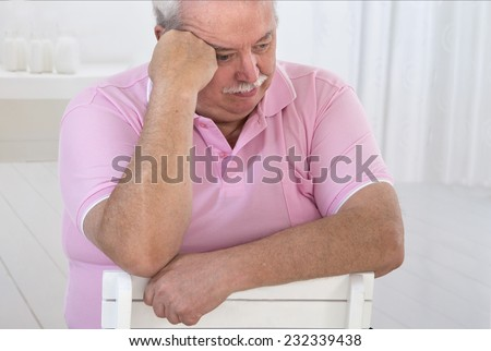 depressed overweight senior man sitting indoor - stock photo