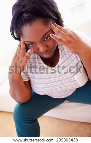 Depressed Overweight Woman Sitting On Sofa - stock photo