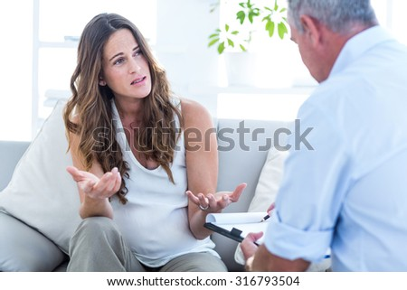 Depressed pregnant woman talking with psychiatrist in clinic - stock photo