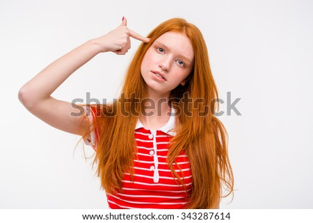Depressed sad redhead young woman with long beautiful hair and a finger to her temple like a gun - stock photo