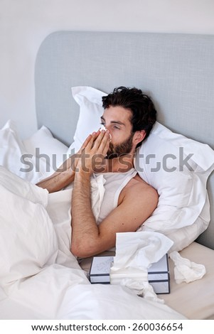 depressed sad sick man with tissues in bed at home - stock photo
