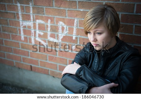 Depressed, sad teen girl sits outside school wall, asking for help - stock photo