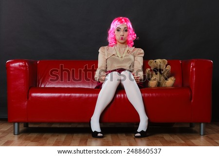 depressed sad woman with teddy bear on sofa in black background