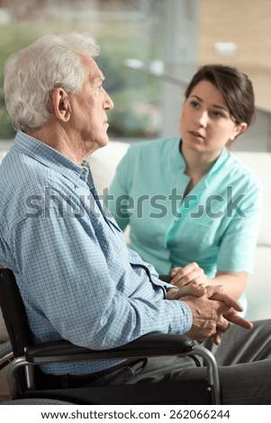Depressed senior man using wheelchair talking with nurse - stock photo