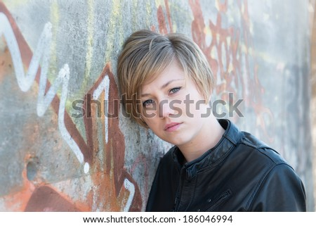 Depressed teen girl in leather jacket, with graffiti wall as background