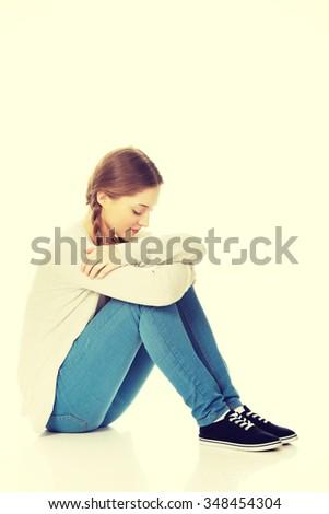 Depressed teen woman sitting on the floor. - stock photo