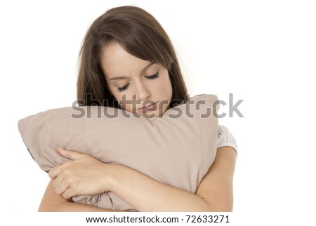 Depressed teenage girl Hugging pillow isolated on white - stock photo