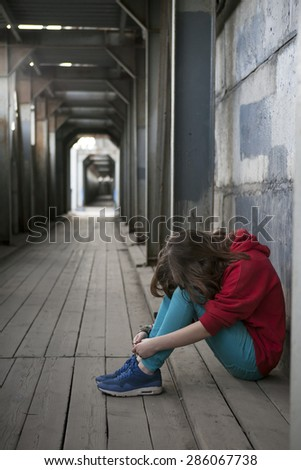 Depressed teenage girl in red hoody with hands over her face - stock photo