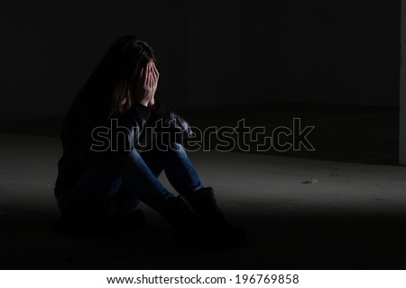Depressed teenage girl with hands over face.