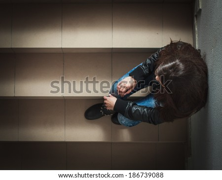 Depressed teenage girl with hands over face sitting on the stairs.
